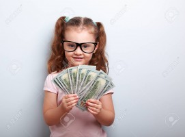 Happy kid girl in glasses holding money in the hand and looking with smile on blue background with empty copy space